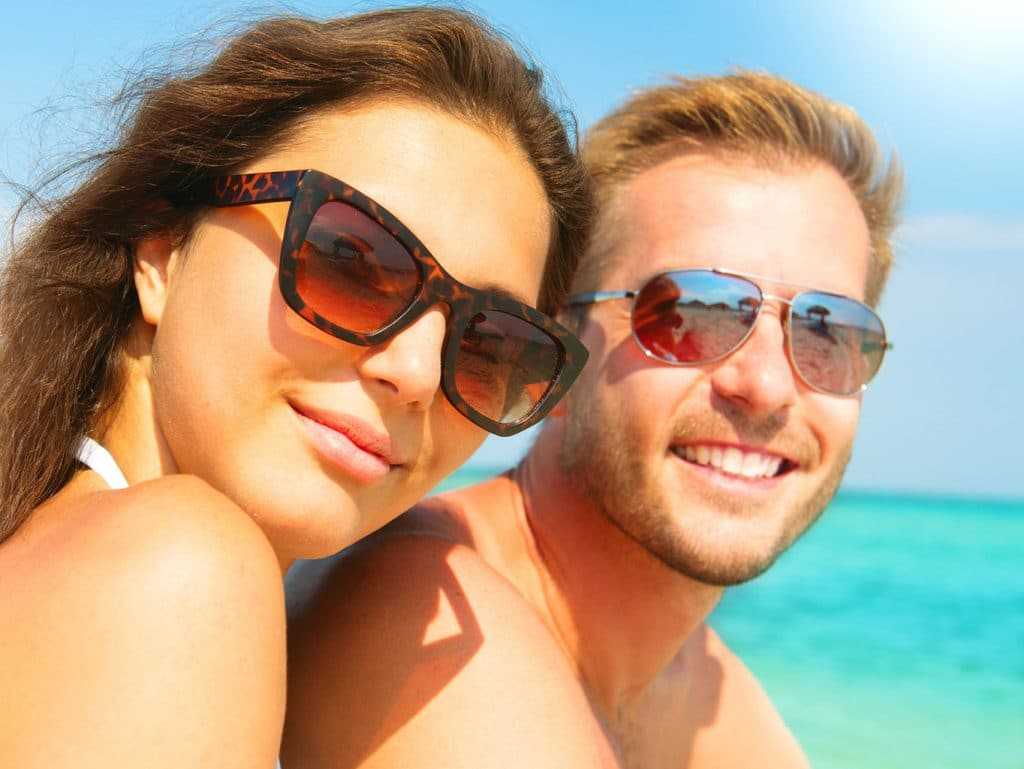 d66d313fdb87f 39944242 - Happy Couple In Sunglasses Having Fun On The Beach
