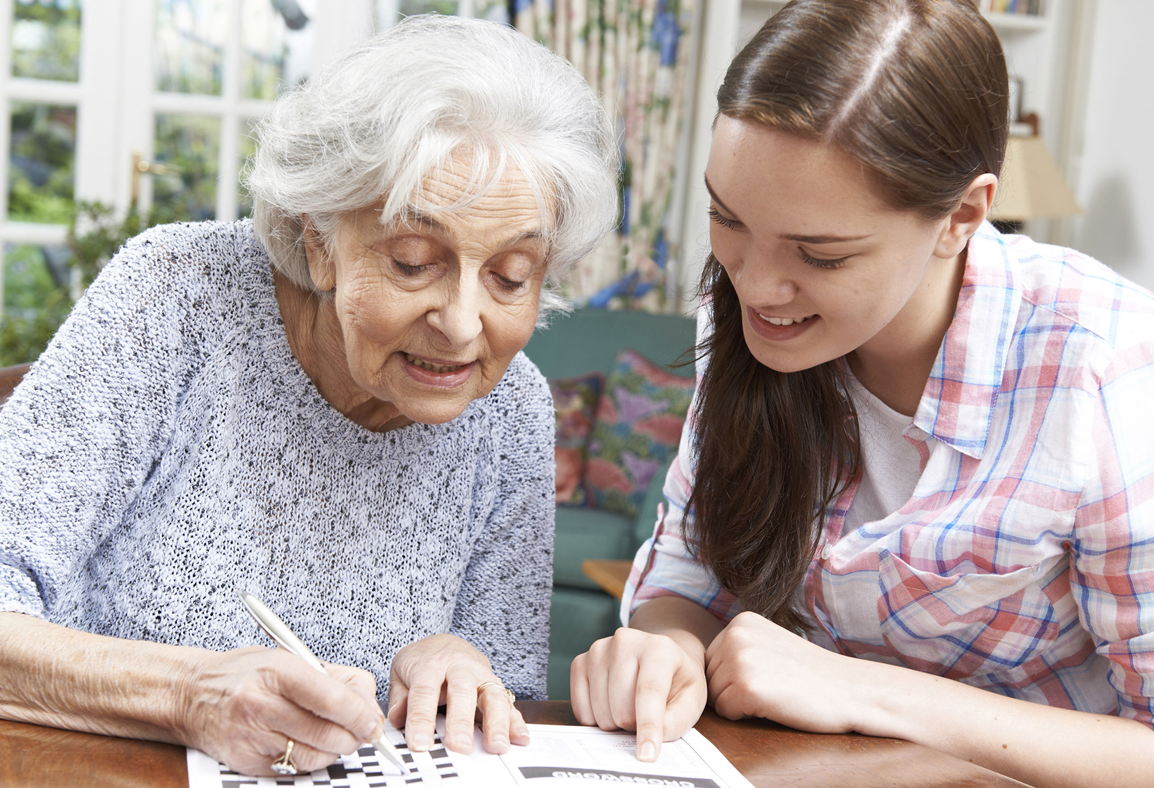 46634496 - Teenage Granddaughter Helping Grandmother With Crossword Puzzle