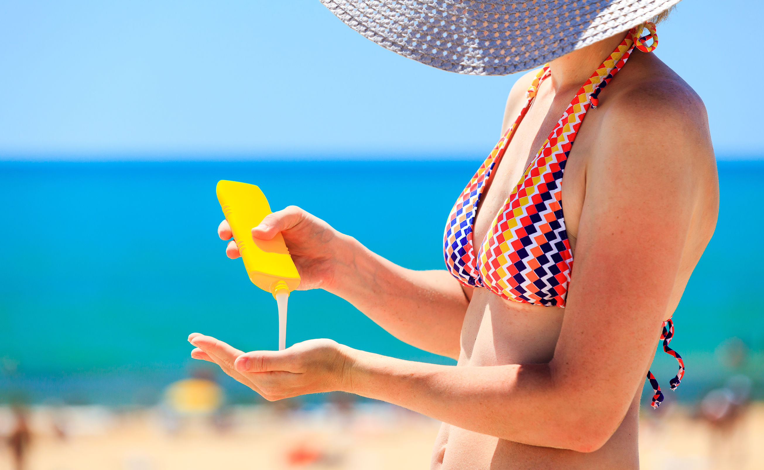 40400729 - Woman Applying Protective Lotion Before Sunbathing At Beach